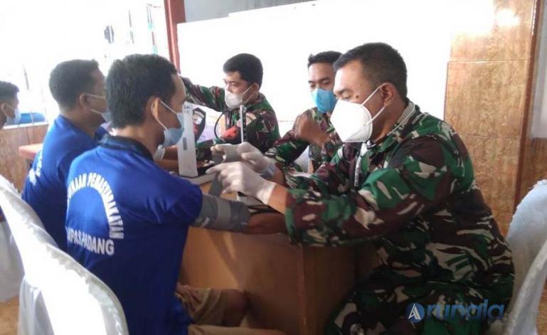 Warga binaan Lapas Klas II/A Padang jalani pemeriksaan sebelum divaksin petugas medis dari Kodim 0312/Kota Padang di Lapas Padang, Sabtu (26/6). (Foto : Derizon)