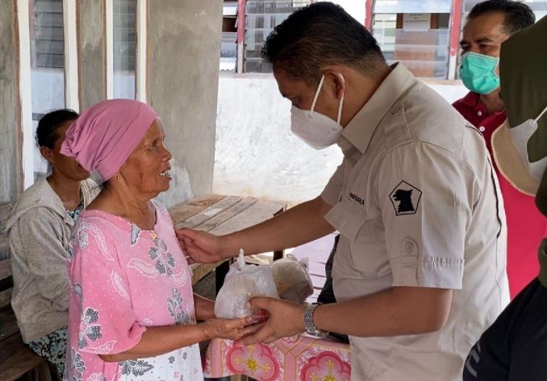 Sekretaris DPD Gerindra Sumbar, Evi Yandri menyerahkan nasi bungkus bantuan Andre Rosiade kepada korban banjir di Kota Padang. (Dok : Istimewa)