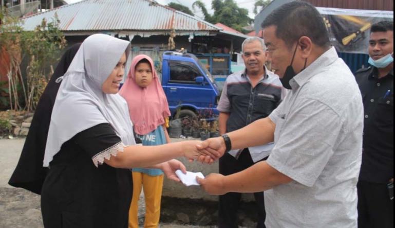 Ketua Fraksi Gerindra DPRD Solok Hafni Hafis menyerahkan bantuan dari Andre Rosiade untuk korban kebakaran di Salimpek, Kabupaten Solok. (Dok : Istimewa)
