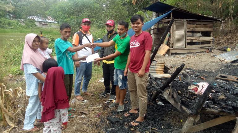 Ketua Tim Media Audy, Nurul Amri bersama Relawan Audy Peduli serahkan bantuan uang tunai kepada Andi, korban kebakaran di Muaro Paneh Kabupaten Solok, Kamis (18/6). (Dok : Istimewa)