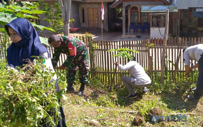 Sertu Ali Darwis bersama mahasiswa bersihkan taman PKK Kampung Padang Panjang I, Kenagarian Kambang Utara, Kamis (20/8). (Foto : Snm)
