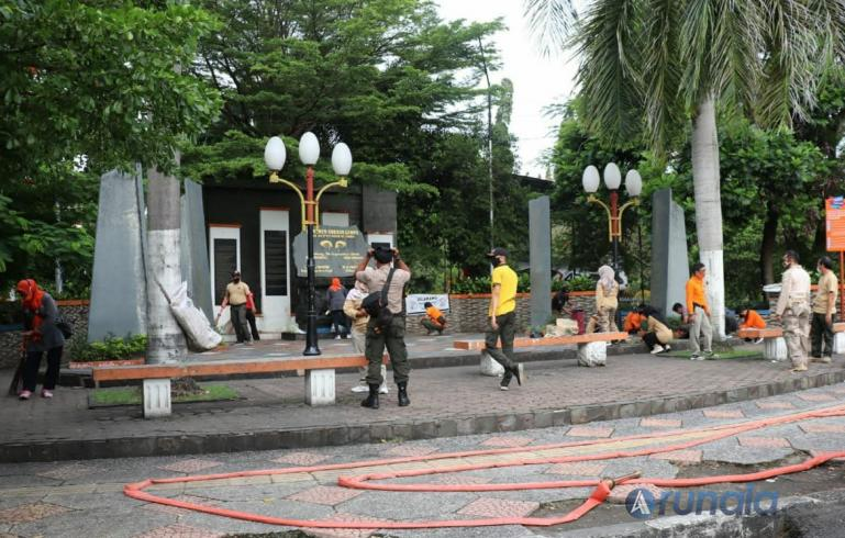 Petugas BPBD Kota Padang bersama relawan membersihkan Tugu Gempa 30 September, Selasa (28/9). (Foto : Derizon)