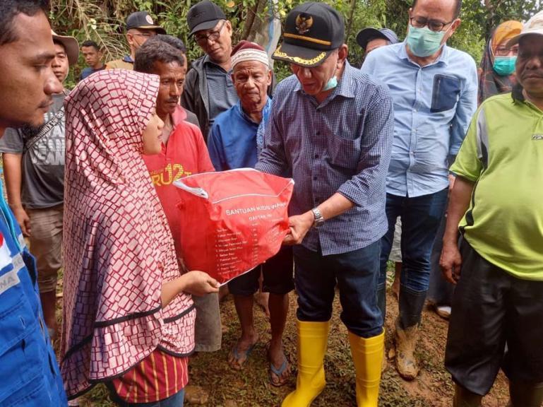 Bupati Pessel, Rusma Yul Anwar ketika menyerahkan bantuan kepada salah seorang pemilik rumah yang rusak akibat longsor, Minggu (19/9). (Dok : Istimewa)