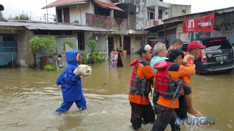 Tim Basarnas saat mengevakuasi warga yang rumahnya terendam banjir di kawasan Jundul Rawang, Kecamatan Padang Selatan, Kamis pagi (10/9). (Foto : Dyz)