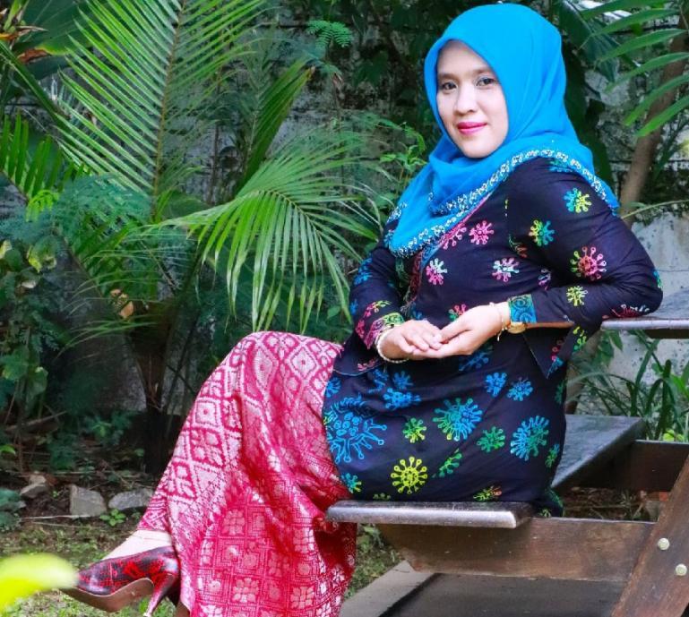 Komisioner KI Sumbar, Tanti Endang Lestari menyempatkan diri menjadi model untuk busana Batik bermotif virus corona hasil kreasi Dewi Busana Lunang. (Dok : Istimewa)