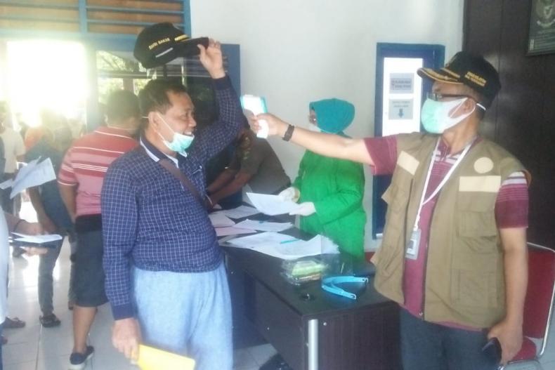 Koordinator Satgas Covid Matra Laut Sumbar, Yosmeri memeriksa suhu tubuh salah seorang penumpang KMP Ambu-Ambu yang akan berangkat ke Tuapejat, Mentawai, Minggu (31/5). (Dok : Istimewa)