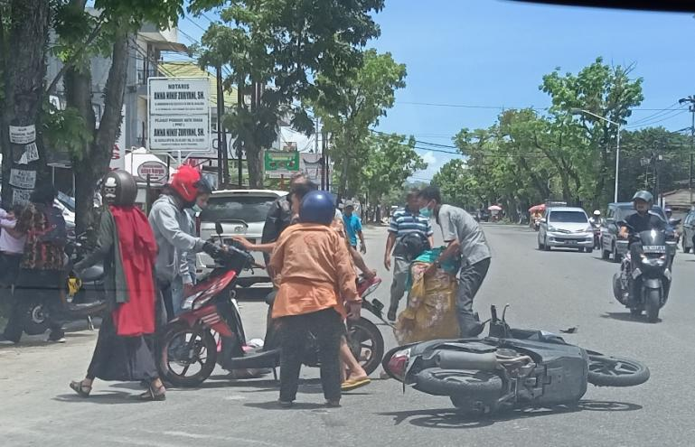 Warga berusaha memindahkan dua motor yang alami kecelakaan di Jalan S Parman Padang, Rabu siang (16/3). (Foto : Arzil)