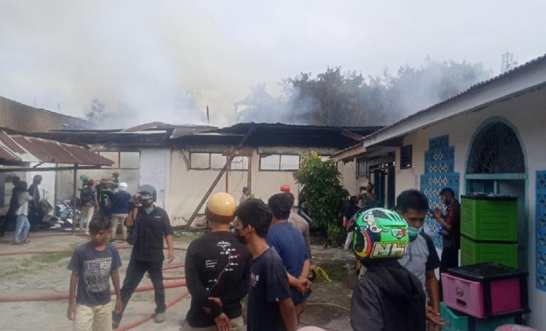 Sejumlah warga menyaksikan kepulan asap yang ada di gudang milik Dinas Pertanian Sumbar yang terbakar Kamis siang (5/8). (Dok : Istimewa)