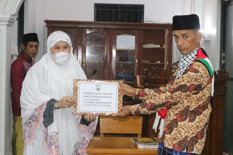 Ketua Tim 3 Safari Ramadhan Pemko Pariaman, Fitri Nora menyerahkan donator kepada pengurus Mesjid Darul Muttaqin Desa Koto Maparak, Rabu (21/4). (Dok : Istimewa)