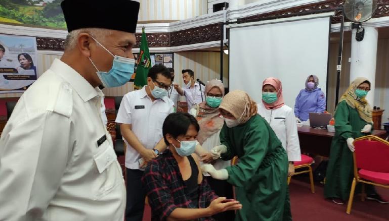 Gubernur Mahyeldi menyaksikan Ketua IJTI Sumbar John Kambang saat jalani vaksinasi Covid-19 di aula kantor gubernur, Rabu (10/3). (Dok : Istimewa)