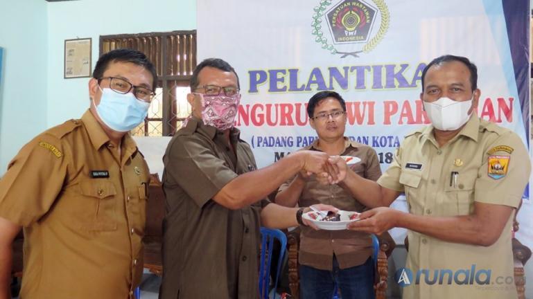 Kepala Dinas Kominfo Pariaman, Hendri membawakan kue ke kantor PWI Pariaman di saat peringatan Hari Pers. Selasa (9/2). (Foto : Arzil)