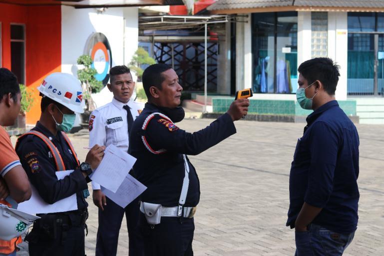 Petugas jaga IPC Teluk Bayur di mengukur suhu tubuh karyawan maupun tamu sebelum memasuki kantor IPC Teluk Bayur, Selasa (17/3). (Foto : Istimewa)
