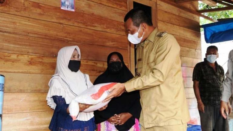 Salah seorang pemilik rumah yang terkena puting beliung terima bantuan dari Wako Pariaman, Genius Umar, Senin (2/8). (Dok : Istimewa)
