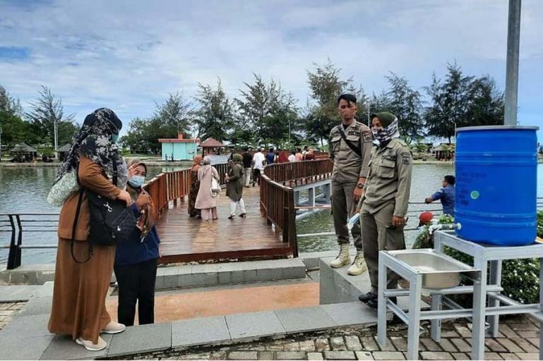 Petugas Sat Pol PP Kota Pariaman lakukan pengawasan Prokes di salah satu tempat wisata di Kota Pariaman, Sabtu (15/5). (Dok : Istimewa)