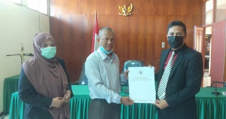 Ketua Majelis sidang KI, Nofal Wiska serahkan putusan sidang sengketa kepada Syarif Isran selaku pemohon, di Padang, Rabu (17/3). (Dok : Istimewa)