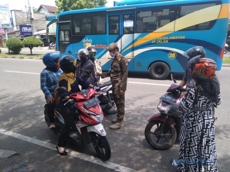 Petugas di check point Samping Hotel Basko Padang hentikan pemotor yang masih berboncengan di saat PSBB diberlakukan, Rabu (22/4). (Foto : Dyz)