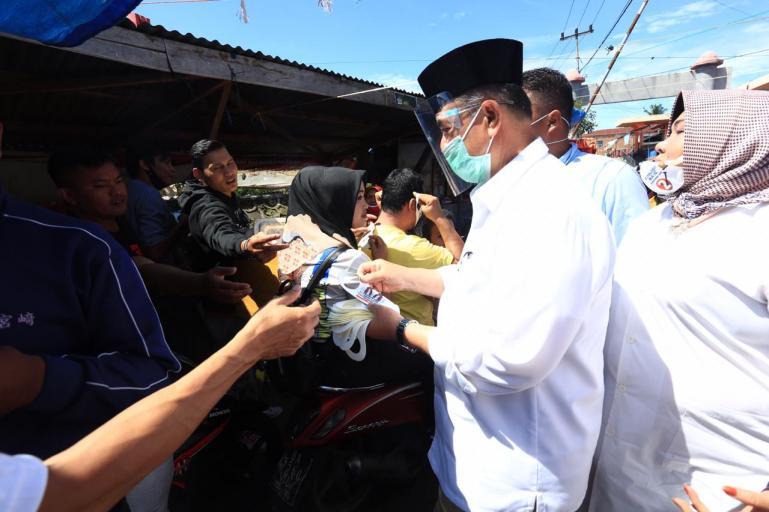 Cagub Sumbar Nasrul Abit saat bagikan masker kepada pencukungnya saat di Pasar Kota Payakumbuh, Jumat (16/10). (Dok : Istimewa)