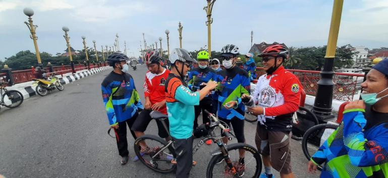 Asisten Deputi III Bidang Pembudayaan Olahraga Kemenpora RI, Maifrizon, bersama jajaran Dispora Sumbar, dan Kota Padang serta Dispora bagikan masker pada warga yang sedang olahraga sepeda di Padang, Selasa (16/2). (Dok : Istimewa)