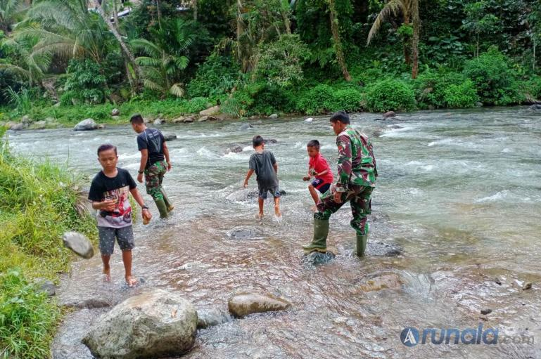Sejumlah anak-anak di Nagari Pancuang Taba terlihat antusias membantu personel TNI mengumpulkan batu untuk pembuatan Tugu TMMD di nagari mereka, Jumat (16/10). (Foto : Rio)