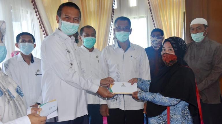 Wako Genius serahkan bantuan Baznas Pariaman kepada delapan warga untuk program bedah rumah, Rabu (17/3). (Dok : Istimewa)