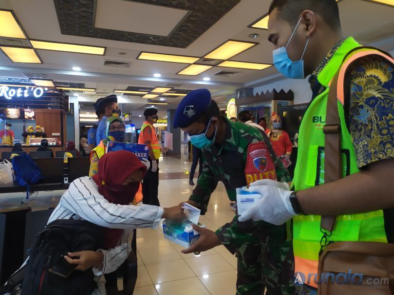 Petugas Bandara BIM dan petugas keamanan membagikan masker dan sarung tangan kepada calon penumpang pesawat di BIM, Jumat (18/9). (Foto : Amz)
