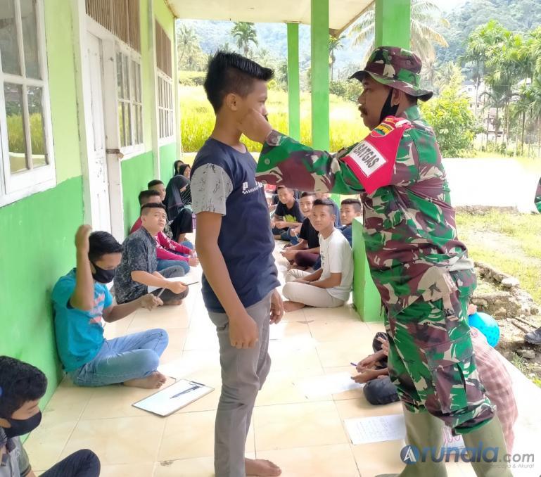 Wadan Satgas TMMD ke-109, Mayor Inf Syawal bagikan masker pada seorang siswaMadrasah Tsanawiyah Swasta Nagari Pancuang Taba, Pessel, Selasa (29/9). (Foto : Rio)