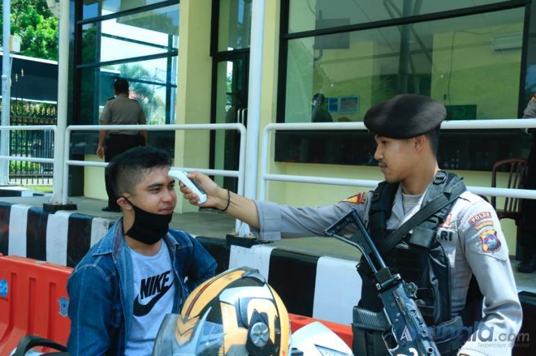 Seorang petugas memeriksa suhu tubuh pengunjung yang datang ke Mapolda Sumbar, Selasa (17/3). (Foto : Dyz)