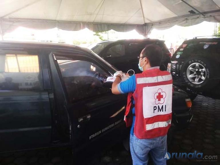 Petugas PMI Sumbar melakukan penyemprotan desinfektan pada salah satu mobil, Selasa (22/9). (Foto : Dyz)