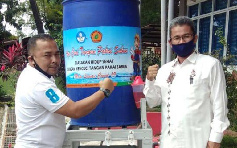 Pembina Sispala Reborn SMA 2 Padang Adrian Toaik serahkan bantuan wastafel dari Politeknik Negeri Padang kepada Kepala SMA 2 Padang Syamsul Bahri, Rabu (24/6). (Dok : Istimewa)