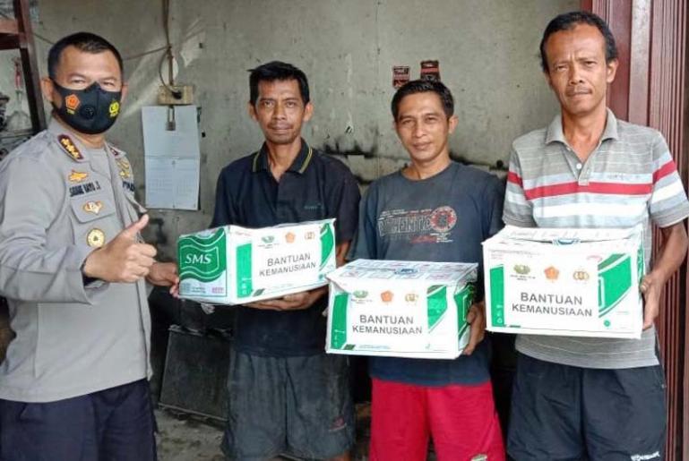 Kabid Humas Polda Sumbar Kombes Pol Satake Bayu, saat menyalurkan bantuan kemanusiaan kepada pekerja bengkel radiator di Jalan By Pass, Kuranji, Senin, (9/11) siang.