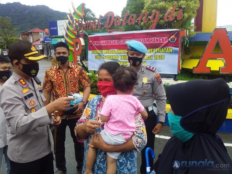 Kapolres Pessel AKBP Sri Wibowo memasangkan masker kepada salah seorang pengendara di Painan, Kamis (10/9). (Foto : Rio)