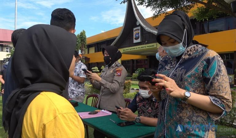 Masyarakat yang terkena razia Perda AKB karena tidak pakai masker saat aktivitas di luar rumah sedang didata petugas di Mapolresta Padang, Jumat (23/4). (Foto : Derizon)
