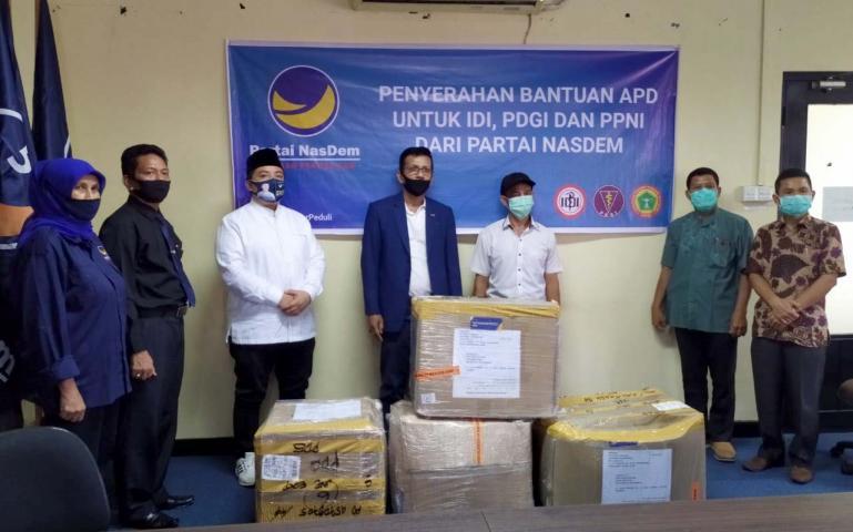 Sekretaris DPW NasDem Sumbar Musmaizer saat serahkan bantuan APD kepada pihak PPNI Sumbar, Jumat (8/5). (Foto : Amz)