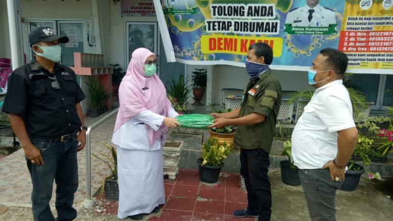 Sekretaris IWO Sumbar Irwandi Teha didampingi pengurusnya serahkan APD kepada dokter yang ada di Puskesmas Andalas, Senin siang (13/4). (Foto : Istimewa)