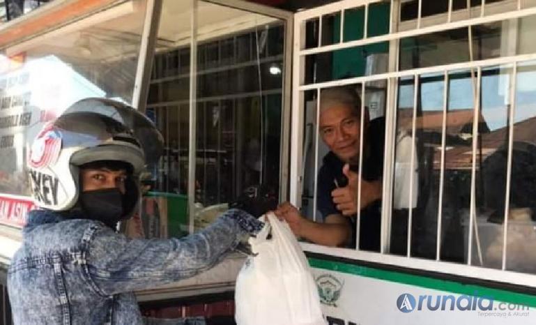 Seorang pasien Covid yang kurang mampu menerima makanan gratis dari Raja Corner saat jalani isolasi mandiri, Sabtu (17/7). (Foto : Derizon)