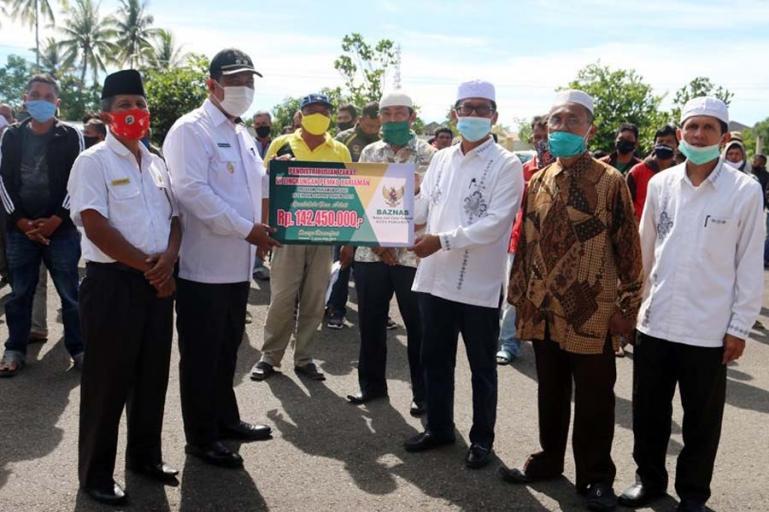 Plt Wali Kota Pariaman, Mardison Mahyuddin didampingi Ketua Baznas Pariaman, Jomohor saat serahkan zakat kepada ratusan tukang ojek dan sopir angkot, Rabu (2/12). (Dok : Istimewa)
