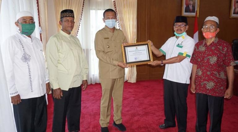 Walikota Pariaman, Genius Umar menerima Piagam Penghargaan dari Ketua Baznas pusat, yang diserahkan oleh Ketua Baznas Kota Pariaman, Jomohor, diruang kerjanya, Balaikota Pariaman, Senin (1/2)