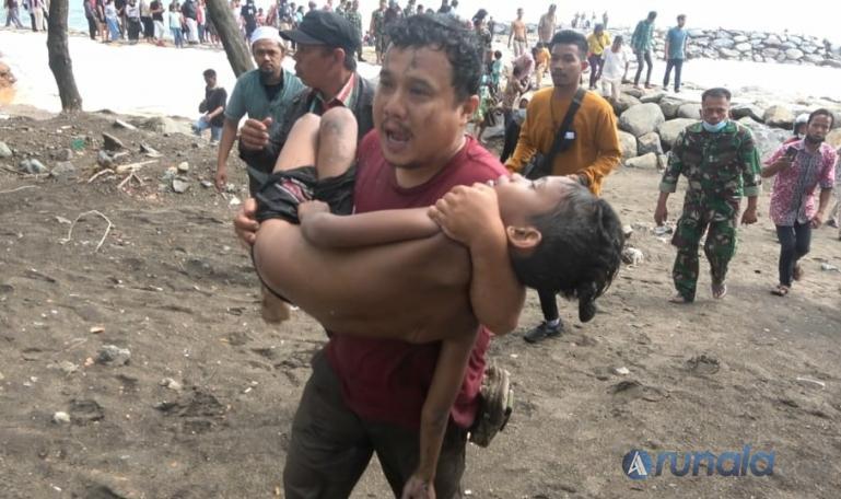 Seorang warga sedang menggotong seorang anak dalam kondisi kritis yang berhasil diselamatkan setelah sempat terseret ombak di Pantai Padang, Selasa (6/7). (Foto : Derizon)