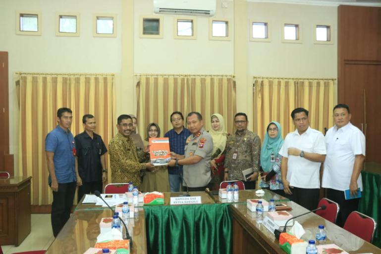 Ketua Bawaslu Sumbar Surya Efitimen serahkan buku Indeks Kerawanan Pemilu (IKP) kepada Kapolda Sumbar Irjen Pol Toni Harmanto, Kamis (12/3).(Foto : Istimewa)