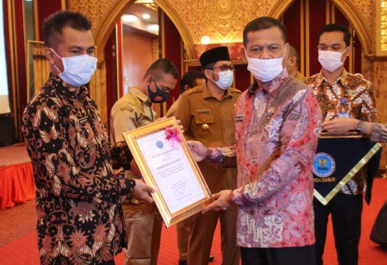 Kepala BNNP Sumbar, Brigjen Pol Khasril Arifin menyerahkan penghargaan kepada pihak yang berkontribusi menekan peredaran narkoba dilingkungannya, Senin (28/6). (Dok : Istimewa)