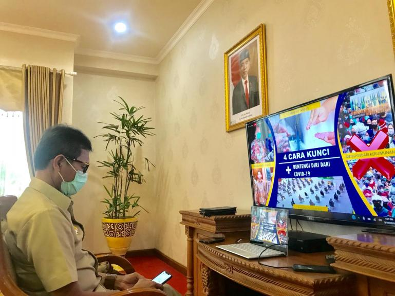 Gubernur Sumbar Irwan Prayitno sedang mendengarkan arahan Mendagri RI Tito Karnavian melalui monitor saat rapat virtual, Senin (10/8). (Dok : Istimewa)