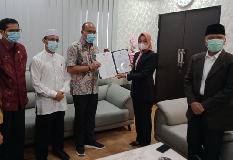 Ketua KPU Sumbar Yanuk Sri Mulyani menyerahkan hasil penetapan pleno kepada Ketua DPRD Sumbar, Supardi, Jumat (19/2). (Dok : Istimewa)