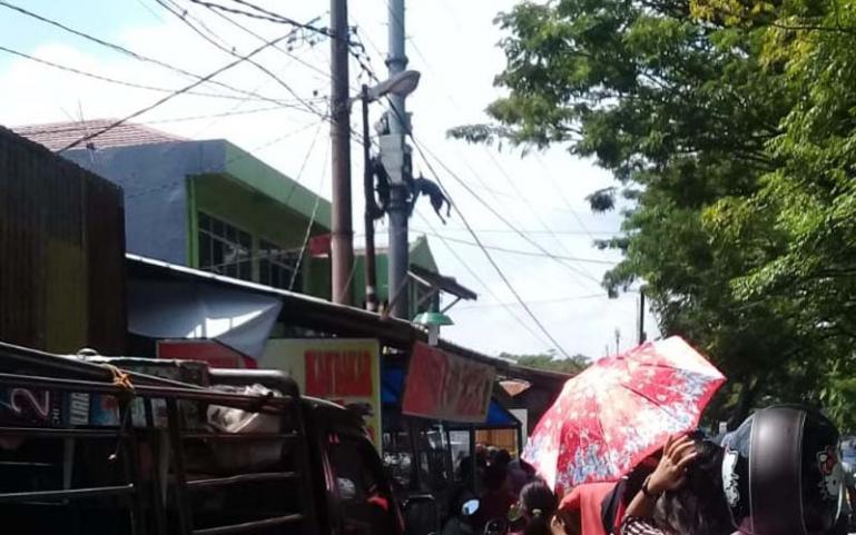Warga menyaksikan korban tersengat listrik yang masih berada di tiang salah satu tower telekomunikasi di kawasan Jalan Ujung Tanah, Padang, Senin (20/7). (Dok : Istimewa)