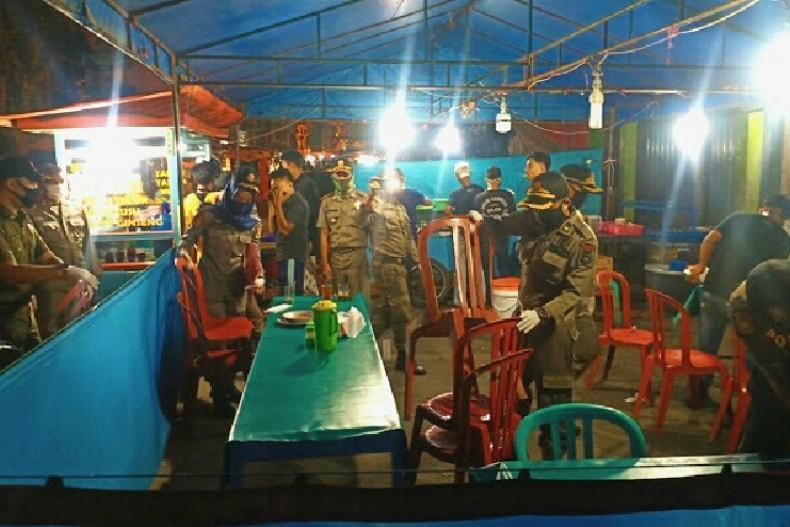 Terlihat tim Satgas gabungan lakukan penertiban pada pedagang yang masih layani konsumen di tempatnya, Sabtu malam (16/5). (Dok : Istimewa)