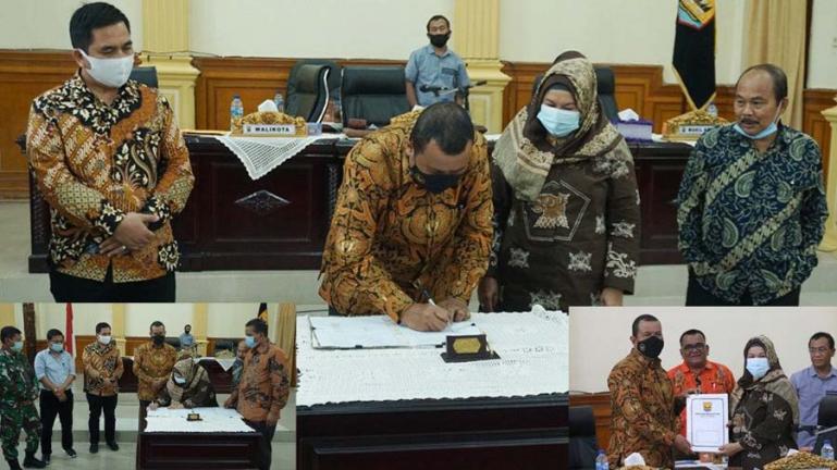 Plt Wali Kota Pariaman, Mardison Mahyuddin menandatangani naskah pengesahan APBD 2021 usai rapat paripurna DPRD Kota Pariamam, Minggu (29/11). (Dok : Istimewa)