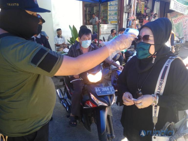 Petugas Pasar Tanah Kongsi, Kota Padang memeriksa suhu tubuh warga yang akan berbelanja di pasar tersebut, Senin (4/5).(Foto : dyz)