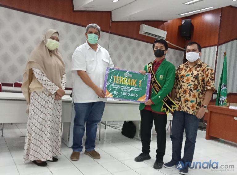 Warek III Unand, Insannul Kamil saat menyerahkan hadiah pada Refa Rahmaddiansyah sebagai terbaik I Pilmapres Unand 2021, Kamis (3/6). (Foto : Arzil)